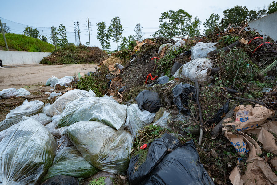 Incoming organic waste typically includes non-compostable contaminants like plastic bags that must be removed.