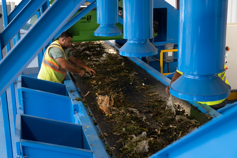 Workers on the sorting line remove contaminants from the pre-shredded feedstock prior to the mixing process.