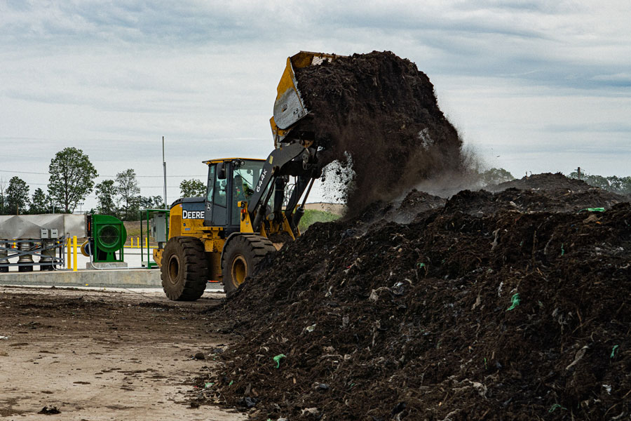 A loader places feedstock onto the aeration pads.
