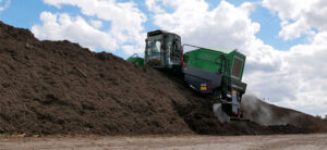 The Komptech Topturn X6000 compost turner creating a tall, peaked windrow.