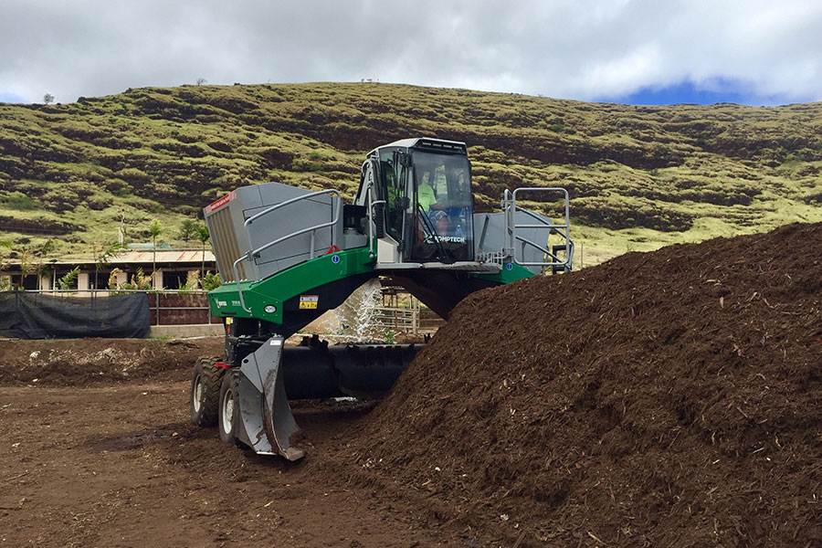 The Komptech Topturn X compost turner creating a tall, peaked windrow.