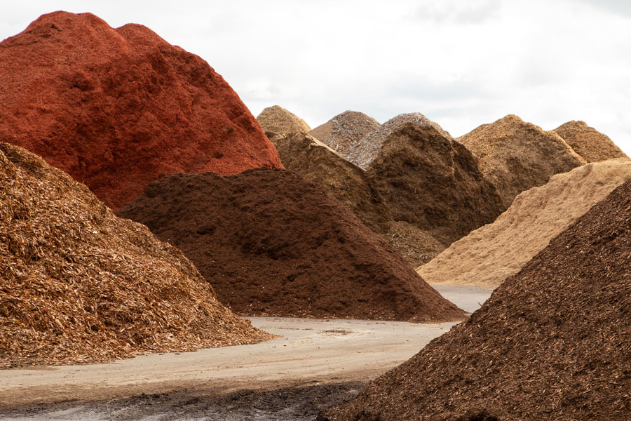 Various piles of colored mulch at a commercial production facility.